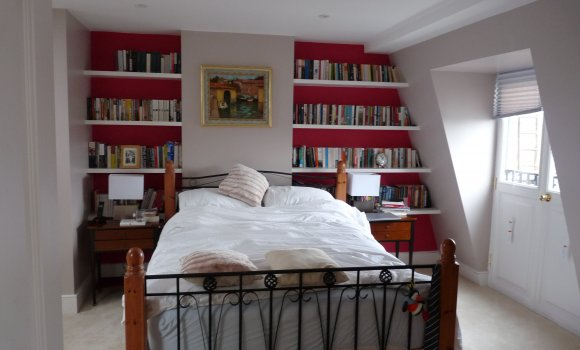 Bedroom with double bed, red wall with bookshelf