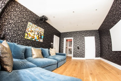 Room for watching movies on the projector. Blue sofa, wooden floor and wallpaper with skull