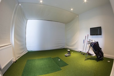 Small room to play a golf with green carpet and white walls