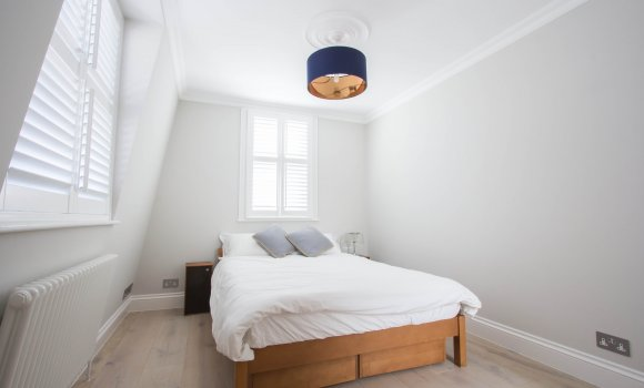White bedroom with double bed and two windows