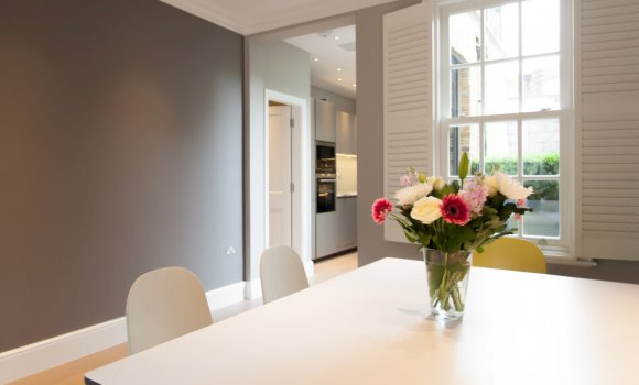 Completely refurbishment dining room with white table, chairs, grey walls and big window